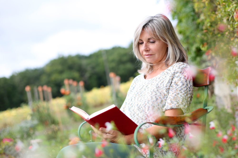 senior reading outside in a field